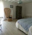 """vue de la chambre Lapérouse, 1 grand lit, 1 fauteuil style """"Emanuelle"""", 1 table avec 2 chaises et 1 armoire patinées dans différents coloris de bleu, 1 miroir et un meuble pour poser la valise."""