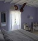 Chambre Occitane avec grand lit, 2 fauteuils, rideau blanc, oeil-de-boeuf