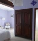 Vue de la chambre Occitane avec lit, 2 fauteuils, et croix occitane