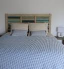 vue de la chambre Lapérouse, 1 grand lit, 1 tête de lit et 2 tables de chevet patinées dans différents coloris de bleu avec lampes de chevets blanches, 2 portes bleues.