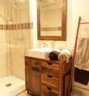 Dans la chambre Toulouse-Lautre, meuble de salle de bain patiné en marron avec lavabo, douche à l'italienne, miroir, échelle décorée avec serviettes de bain.
