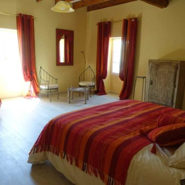 Vue de la chambre Safran, lit, banquette à l'orientale, 2 fauteuils, table basse, miroir rouge