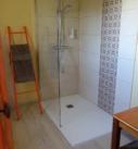 Salle de bains chambre Saffran, avec porte patinée tons orange et doré, douche à l'italienne, échelle orange porte serviettes.